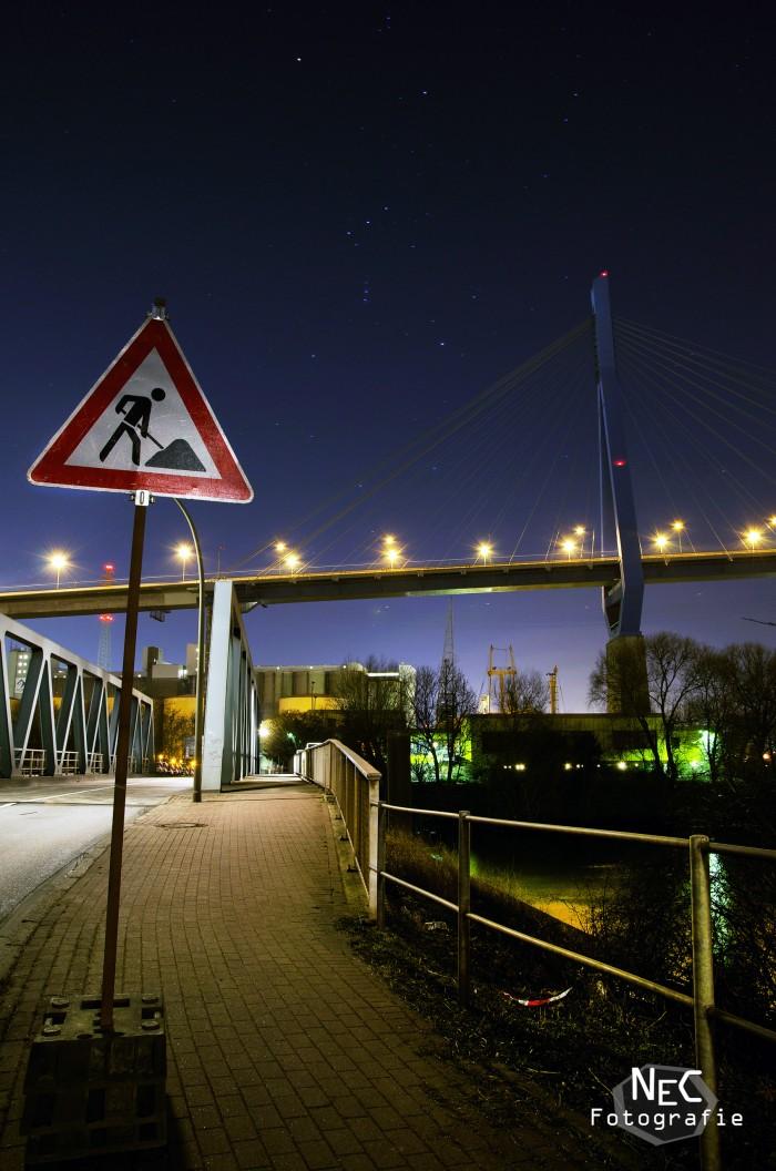 Köhlbrandbrücke im Hafen Hamburg bei Nacht, Baustellenschild